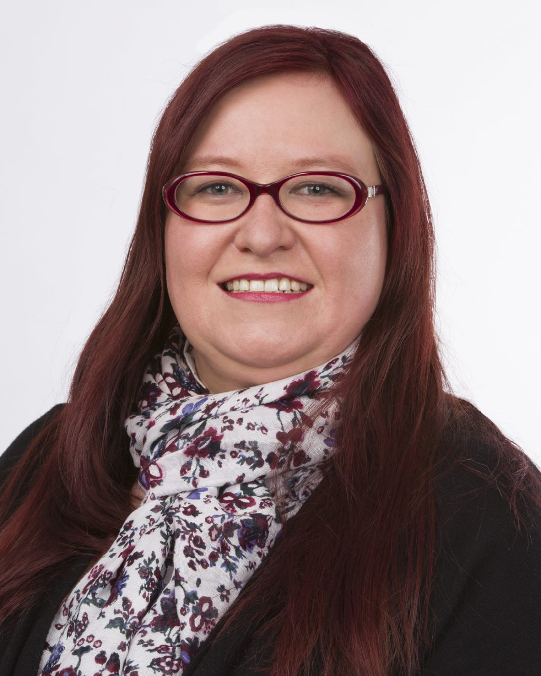 A head-shot of a woman smiling at the camera, she has wine red hair and red-rimmed glasses.