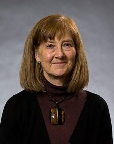 A head-shot of a middle-aged woman with blue eyes and lighter brown hair, she is professionally dressed in a dark maroon turtleneck.